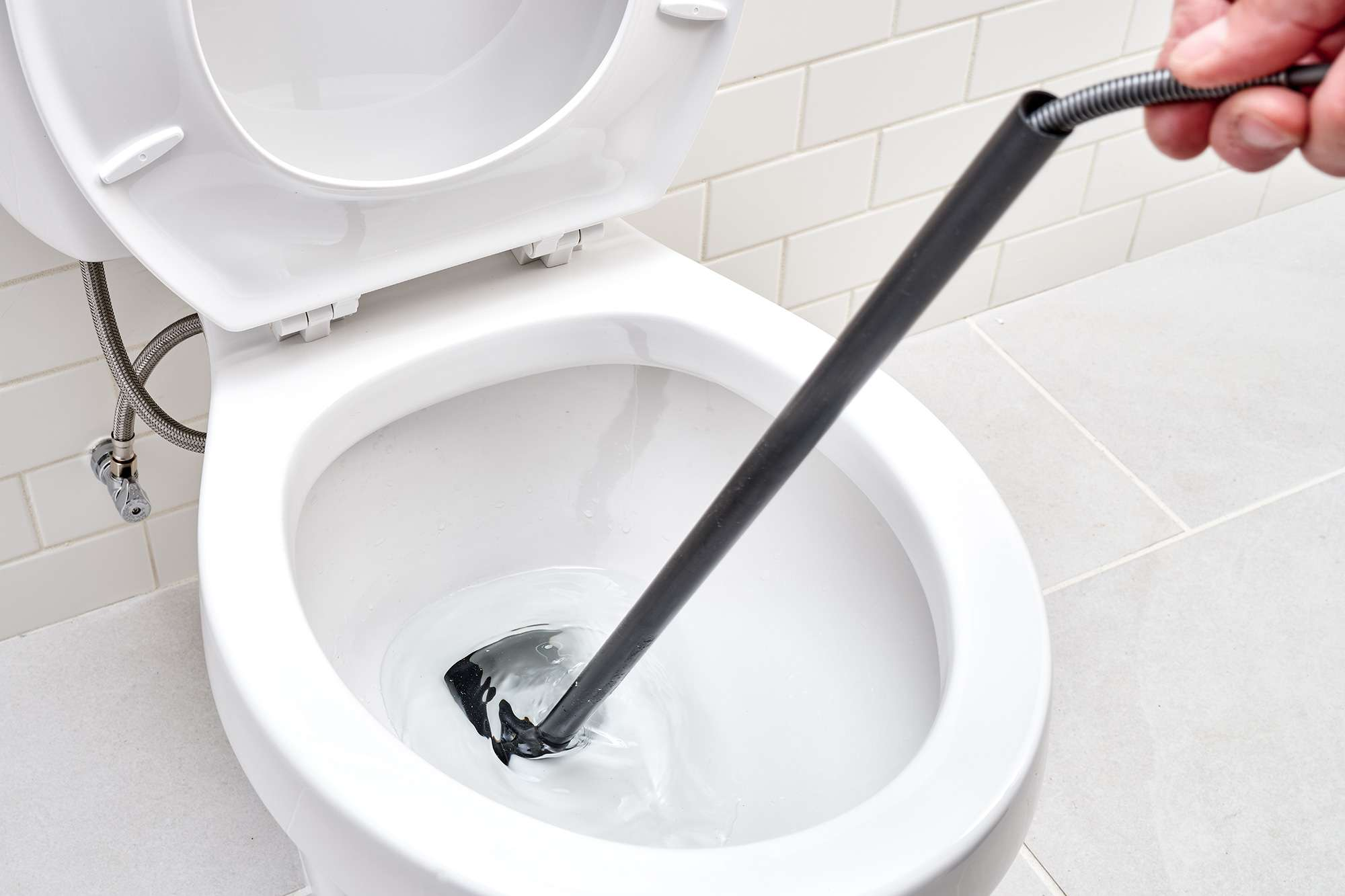 Toilet auger cable pulled back to repeat pushing action