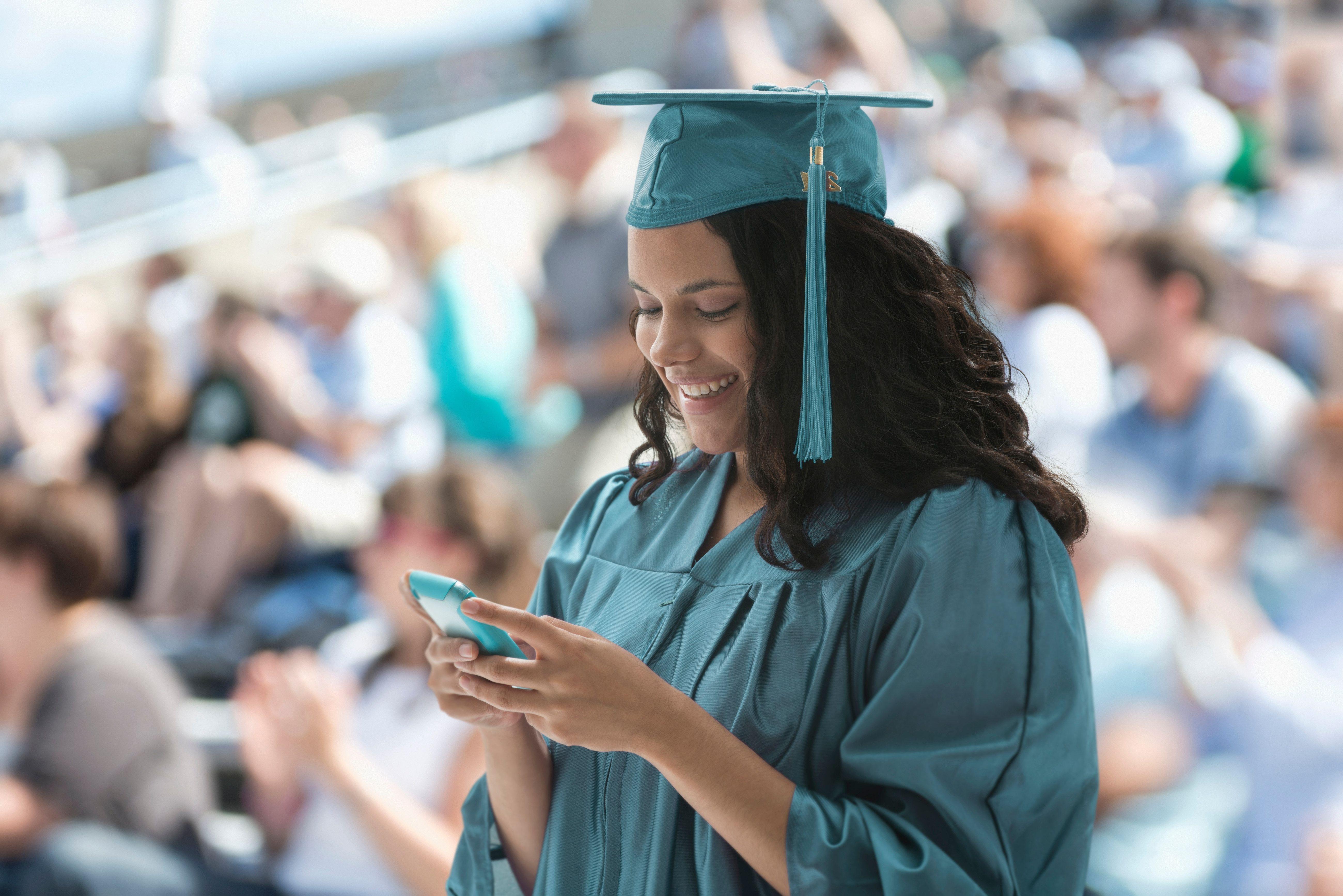 A female graduate using smartphone