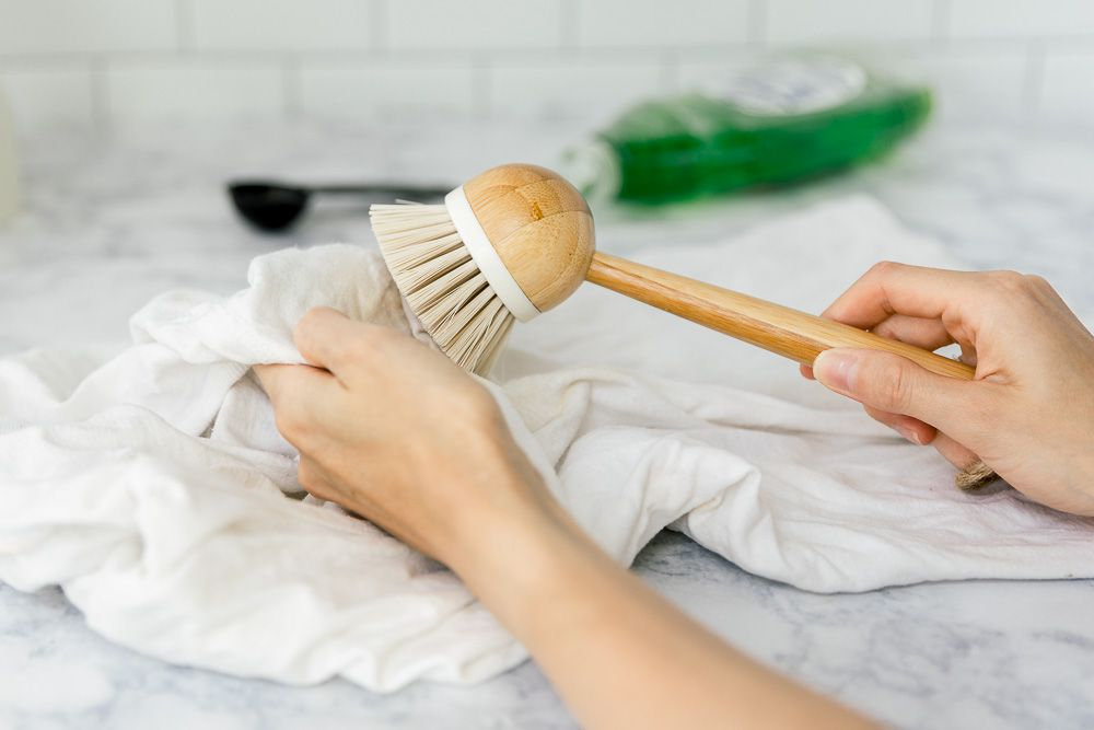 scrubbing the stain with a soft bristled brush