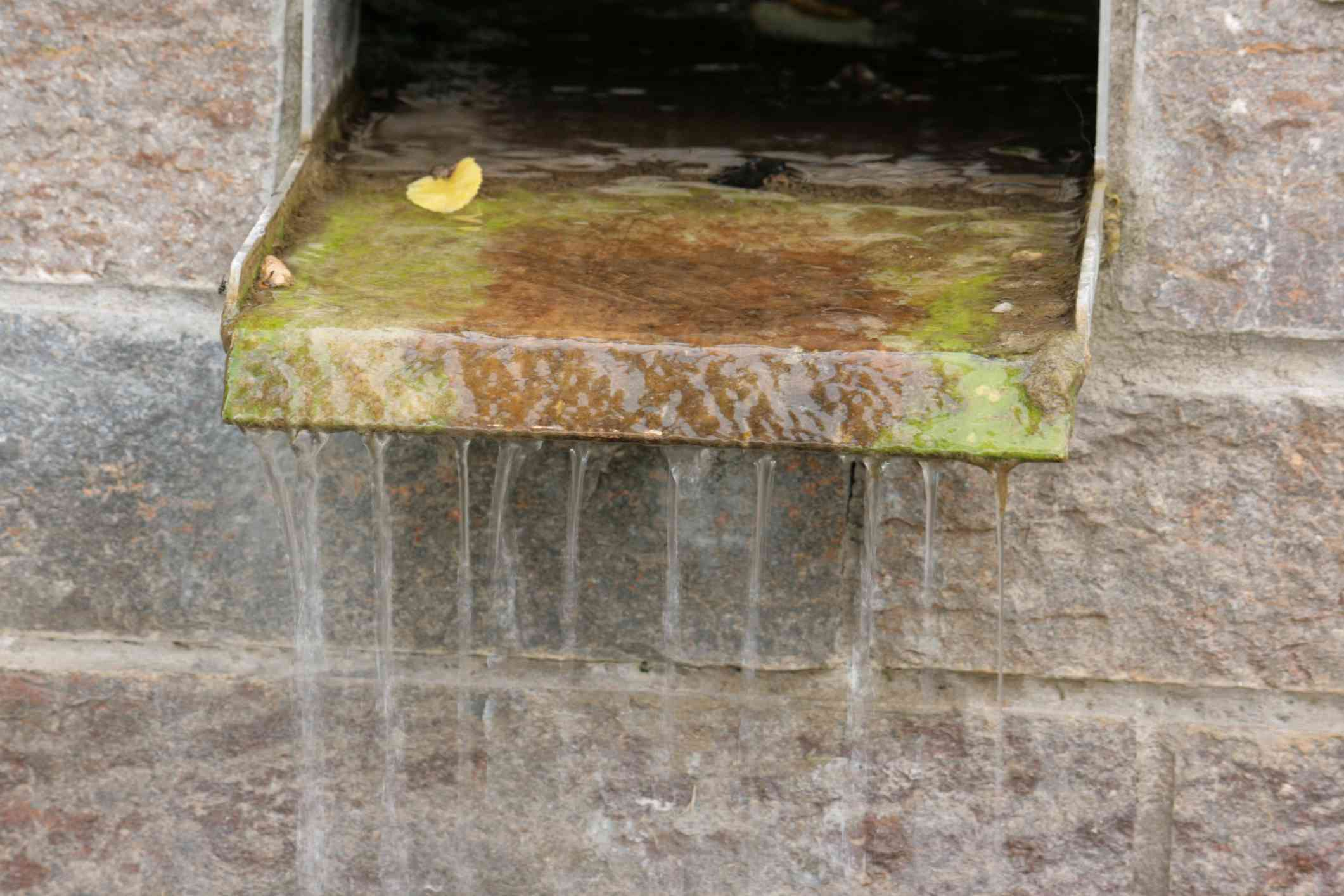 Square rock fountain with water falling over a spillway.