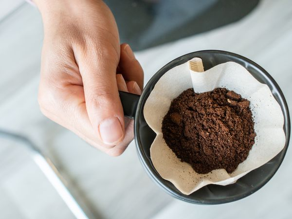 Male hand holding coffee grounds in a filtered coffee basket