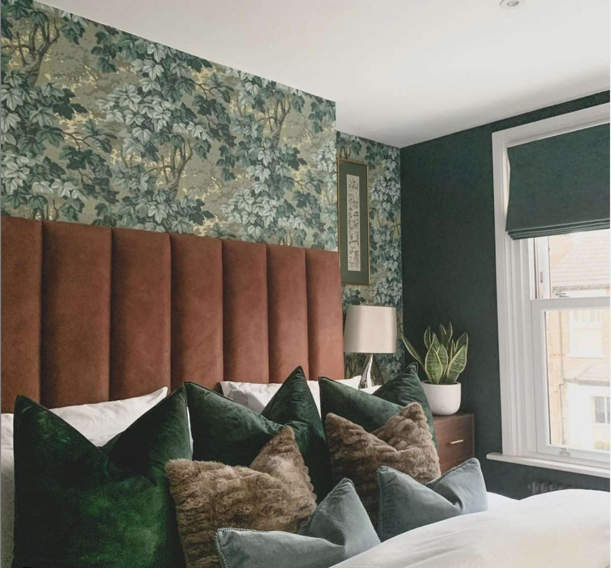 bedroom with burnt orange-red cushion headboard, floral green-ish blue wallpaper, green and blue throw pillows on bed, snake plant in corner