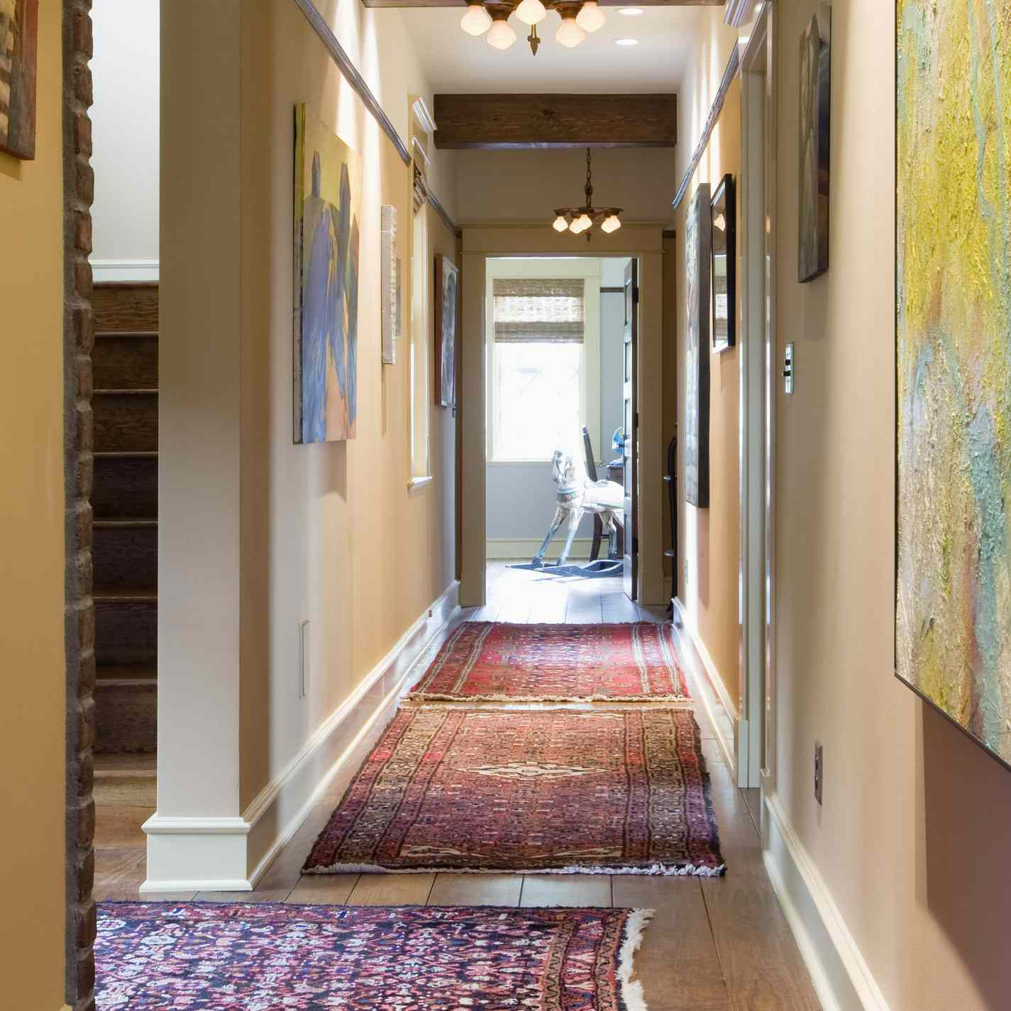 a long hallway with rugs and artwork