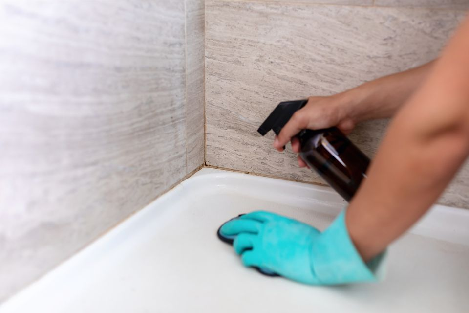 person cleaning tile grout
