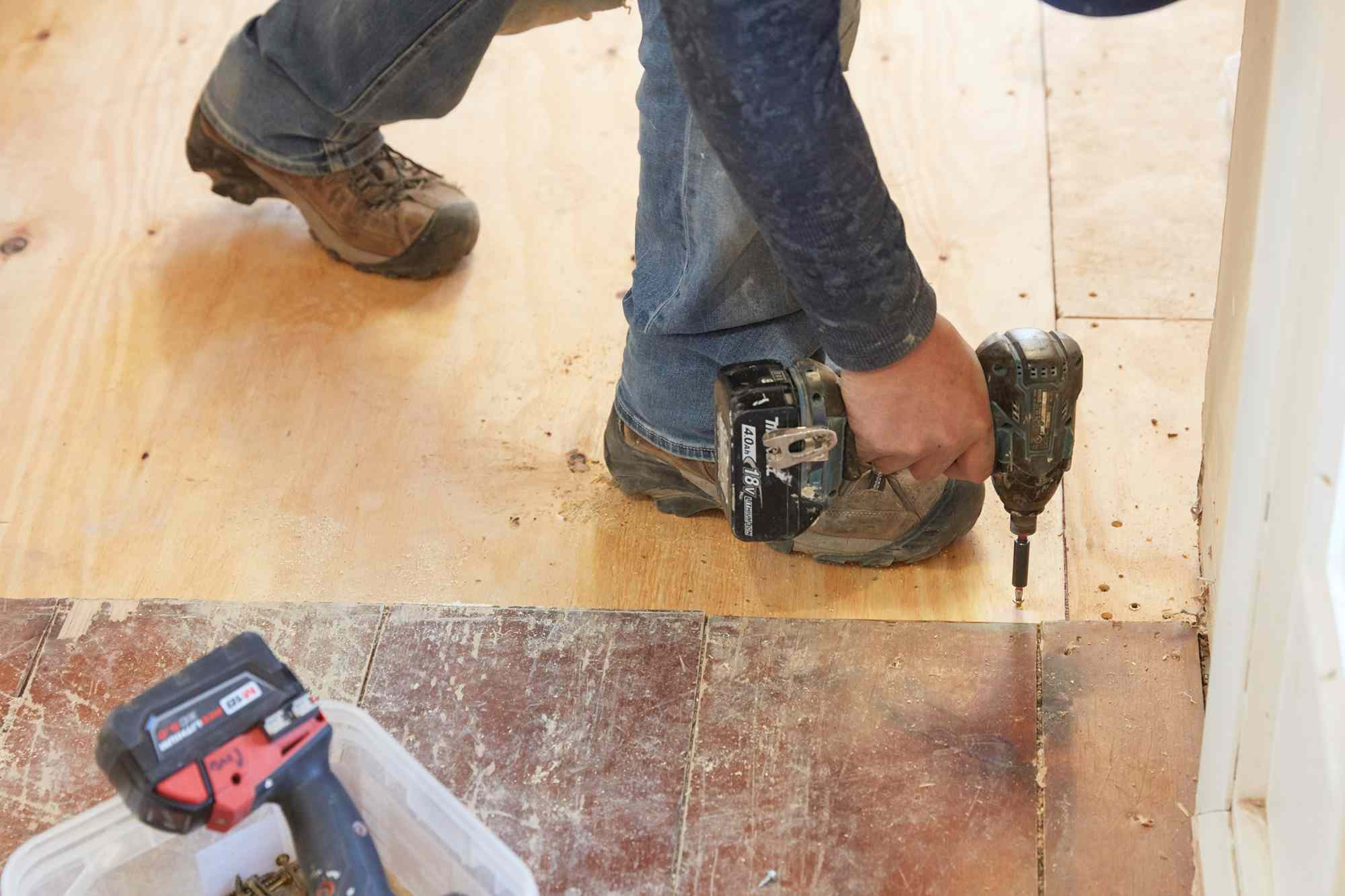 Plywood subfloor installed with with electric drill
