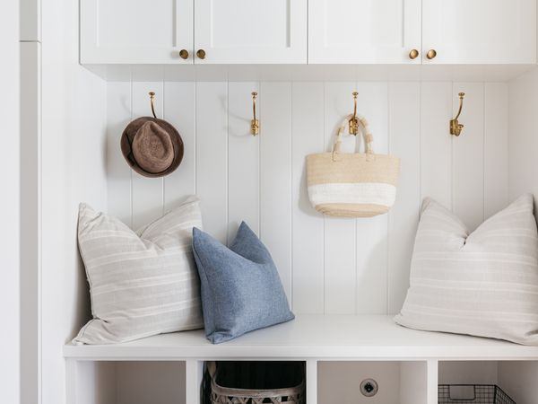 Mudroom with white walls and cabinets storing throw pillows, hat and bag