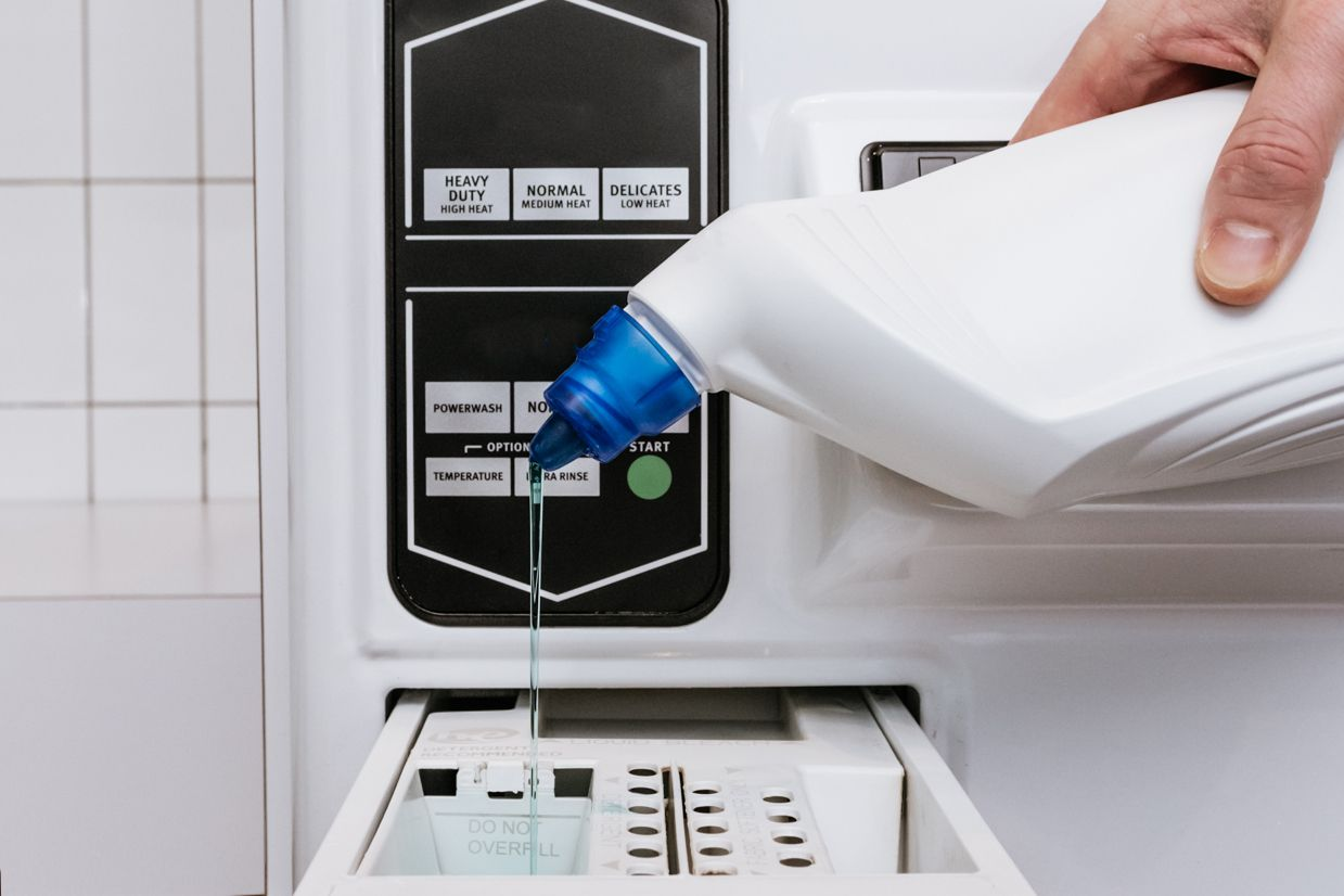 person adding chlorine bleach to a washer dispenser