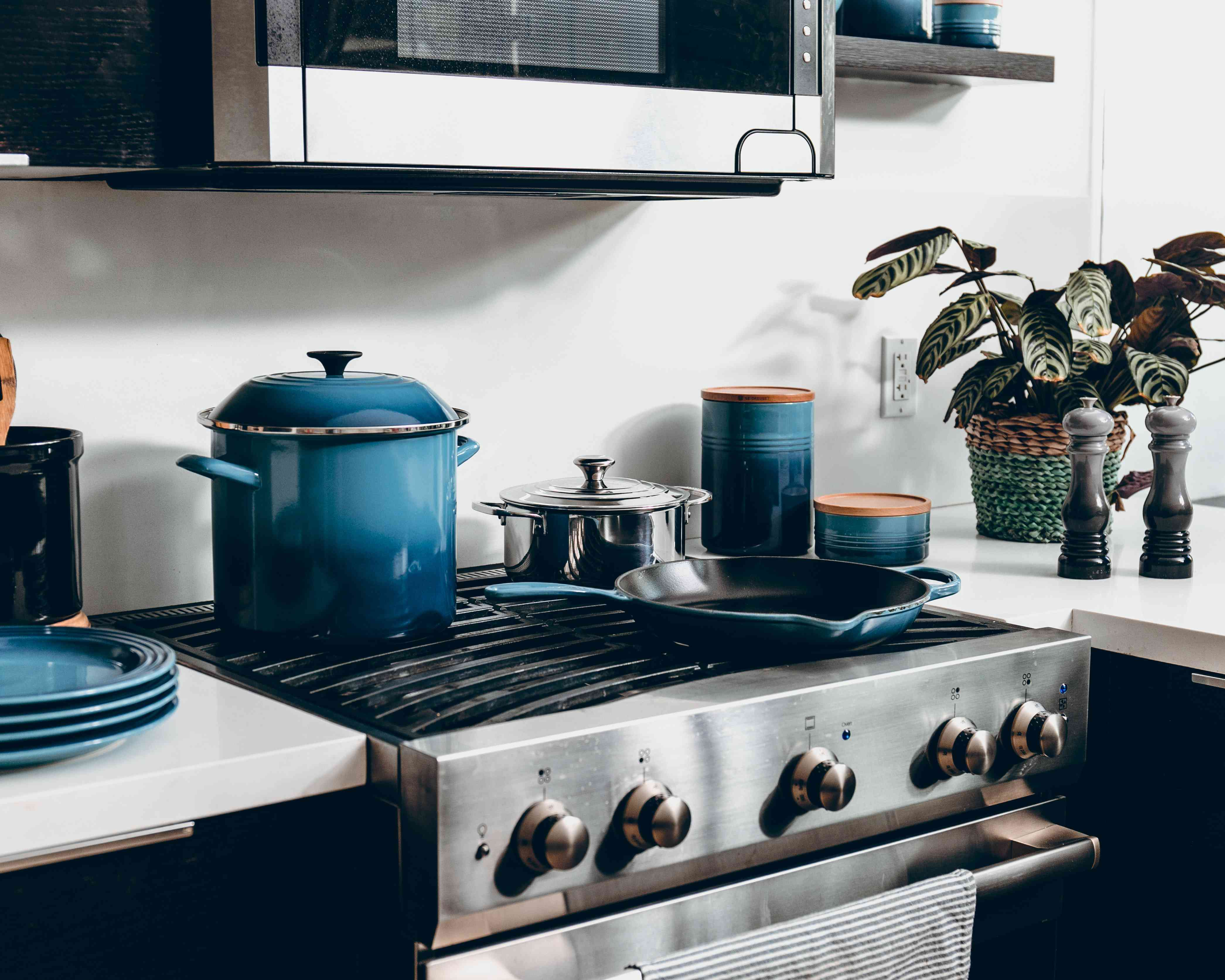 stove with blue pots, pans and plates