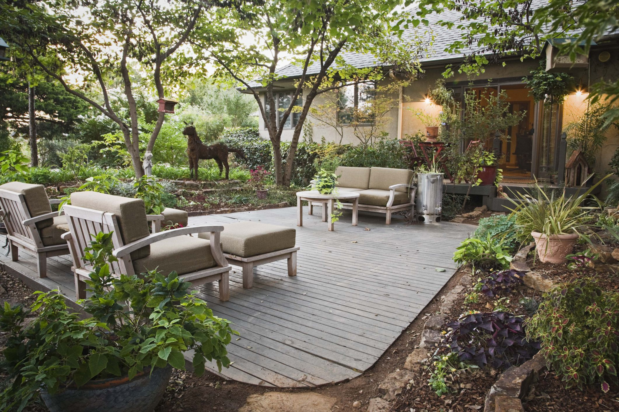 Deck with furniture in back of a single-level house and garden