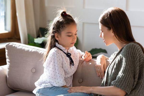 Upset small schoolgirl having trustful conversation with mother.