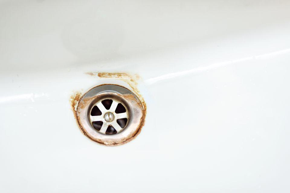 Bathtub drain with rusty water stains around rim