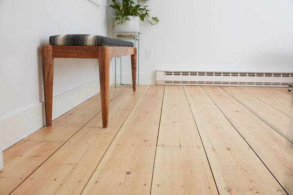 Old hardwood floors refinished with bench and houseplant alongside wall