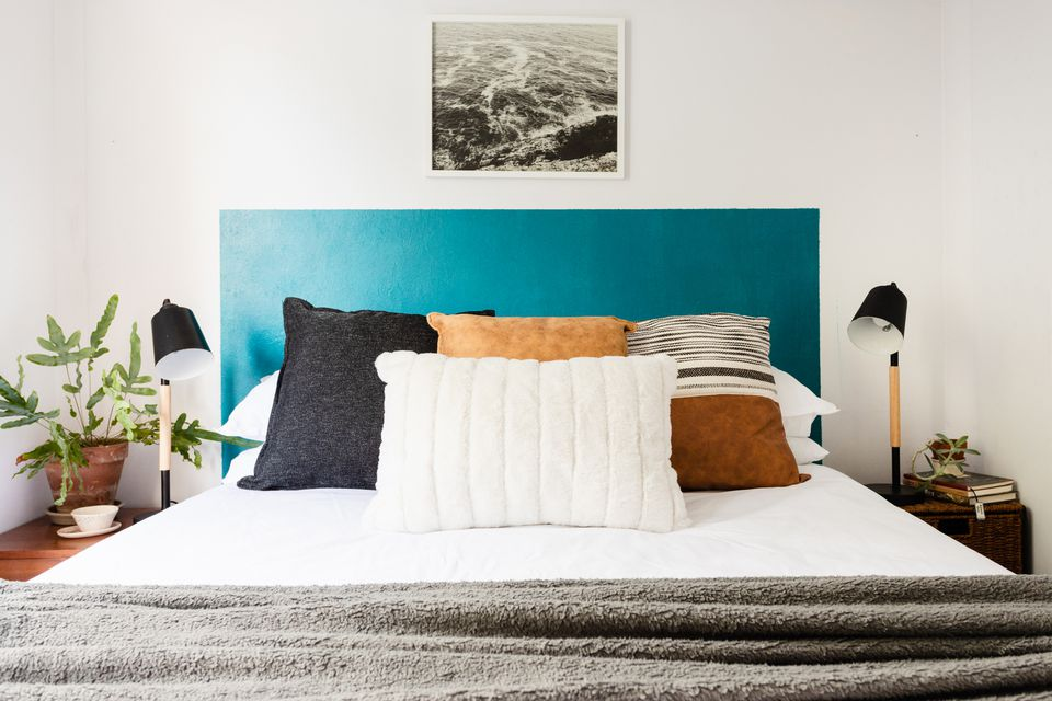 Teal blue DIY headboard behind bed with white, brown and black pillows