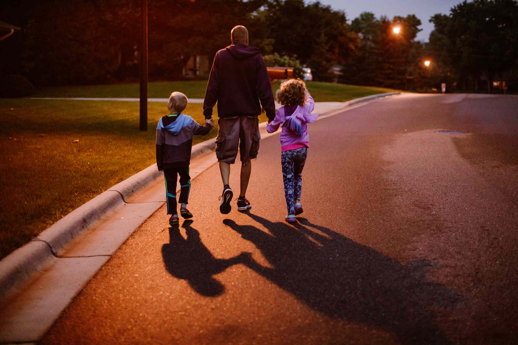 Father, son, and daughter taking a nighttime stroll