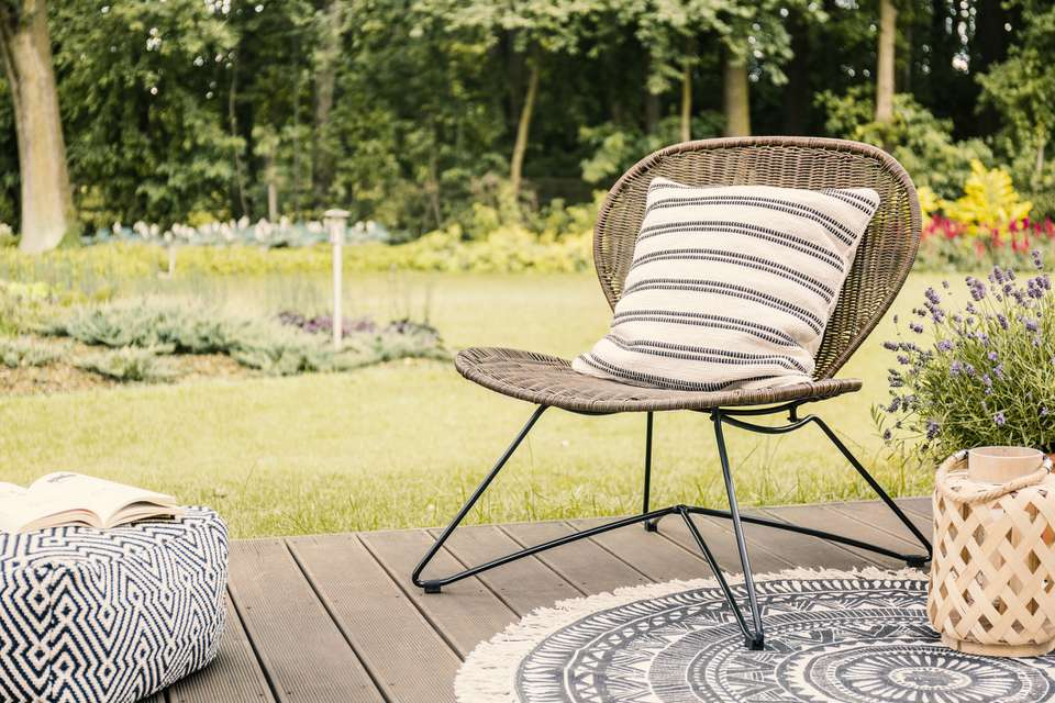 Real photo of a modern garden chair with a white, striped pillow standing on a wooden deck in the garden of a weekend retreat