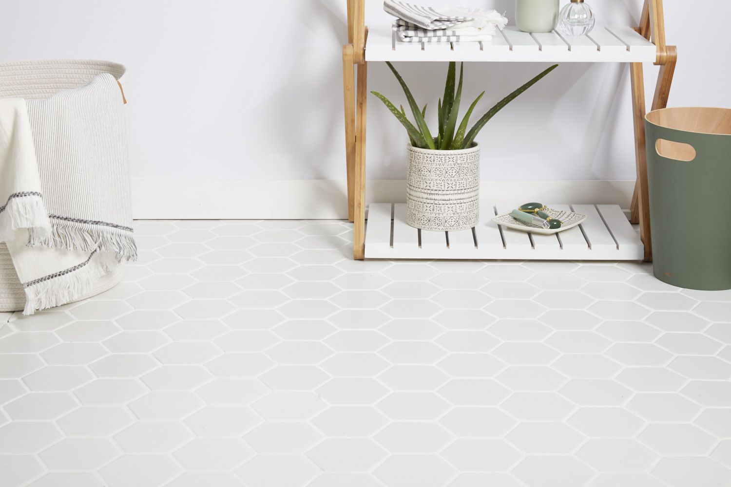 White tile flooring with wooden and white stand with houseplant next to hamper