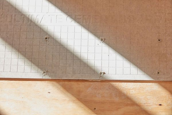 Cement backer board on wooden floor with light and shadows casted across