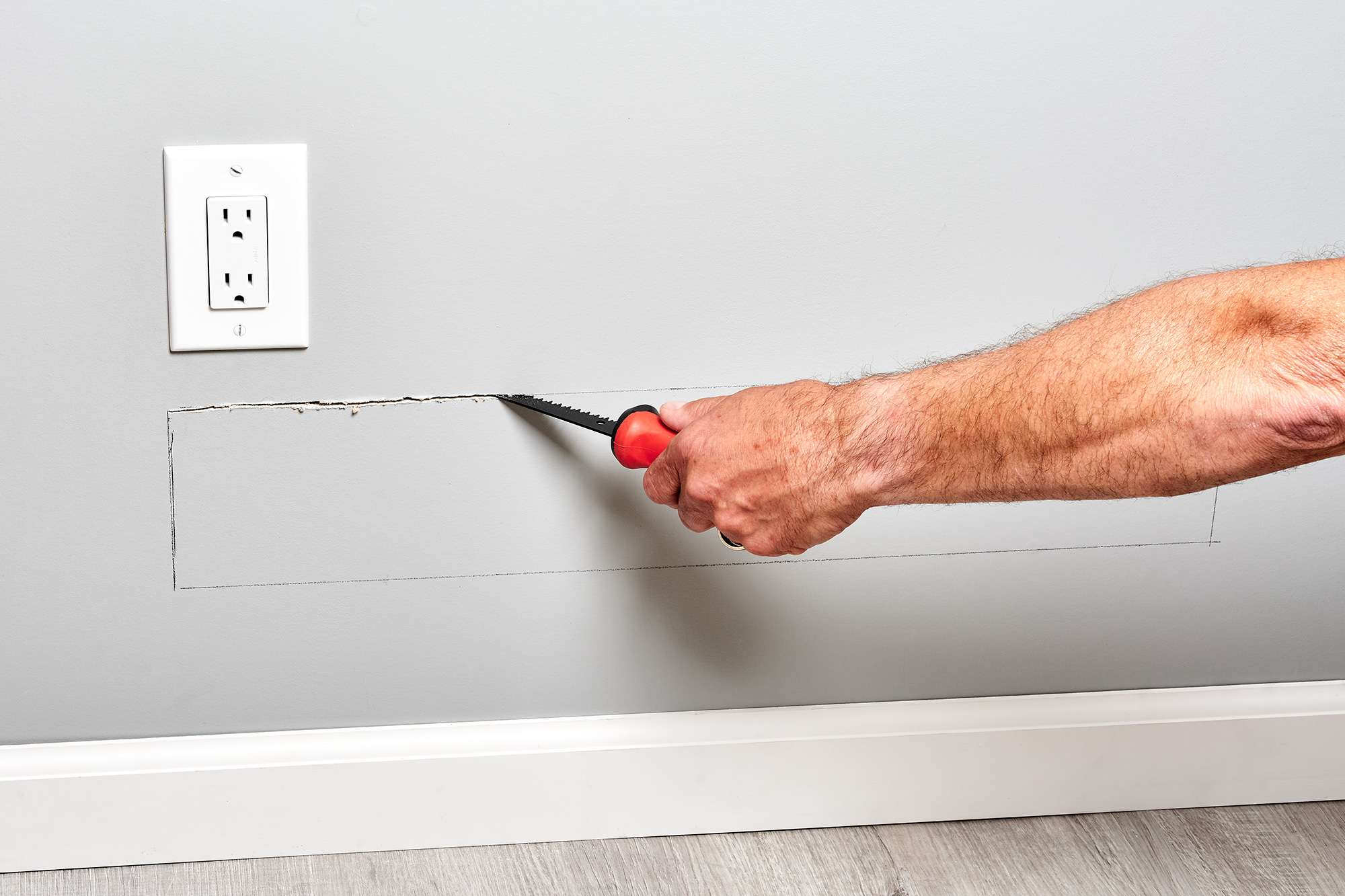 Drywall saw cutting wall open to run electrical wire