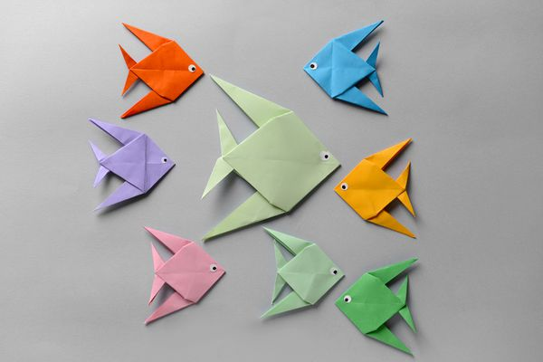 Origami fish on grey background