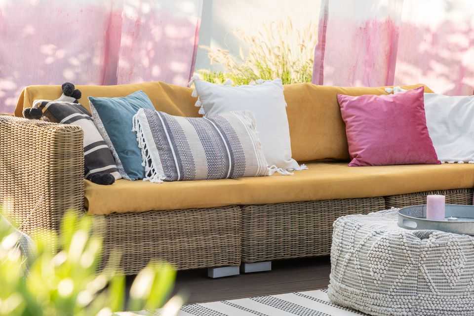 Real photo of colorful pillows on a rattan sofa on the terrace