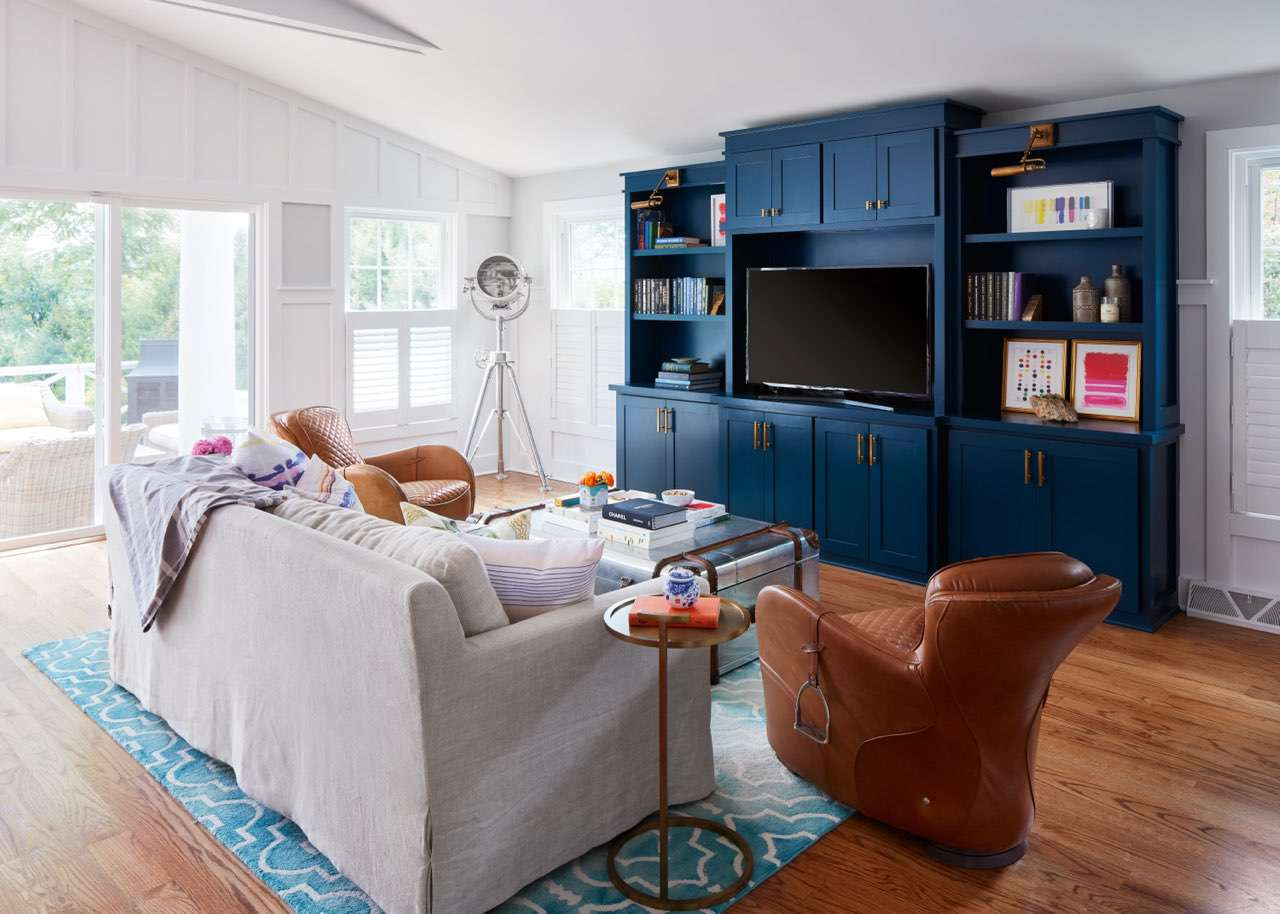 A living room with neutrals as the main colors and navy and pink pops of color