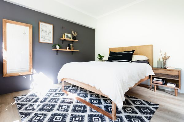 Bed with white cover and black pillow next to wooden headboard, night stand and bright window