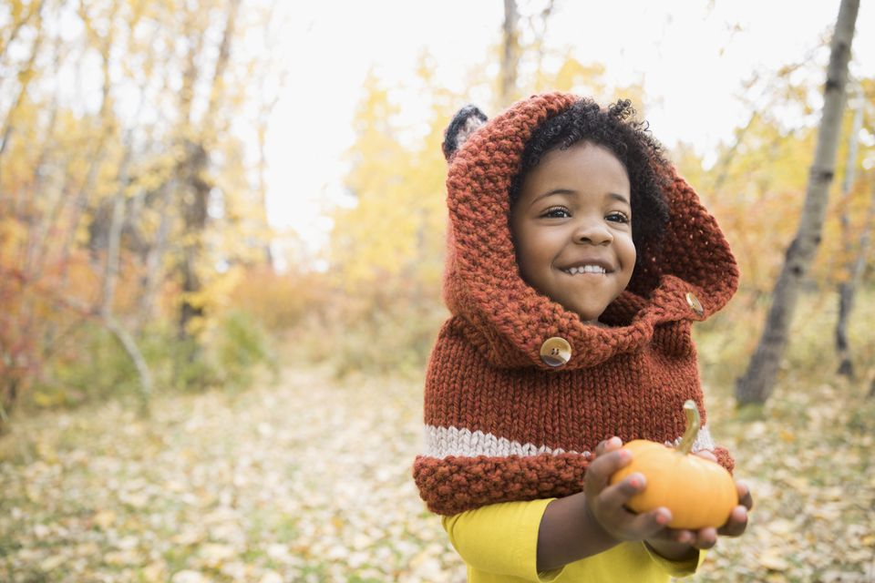 Cute girl holding tiny pumpkin in autumn woods