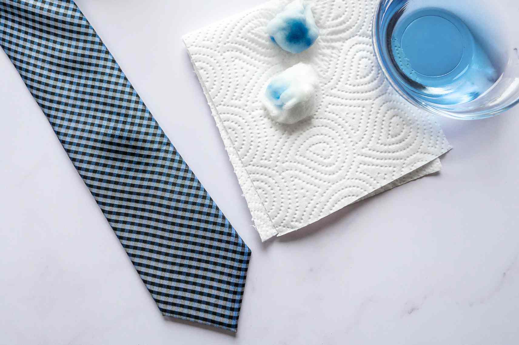 A tie, cotton balls, napkins, and a container of rubbing alcohol