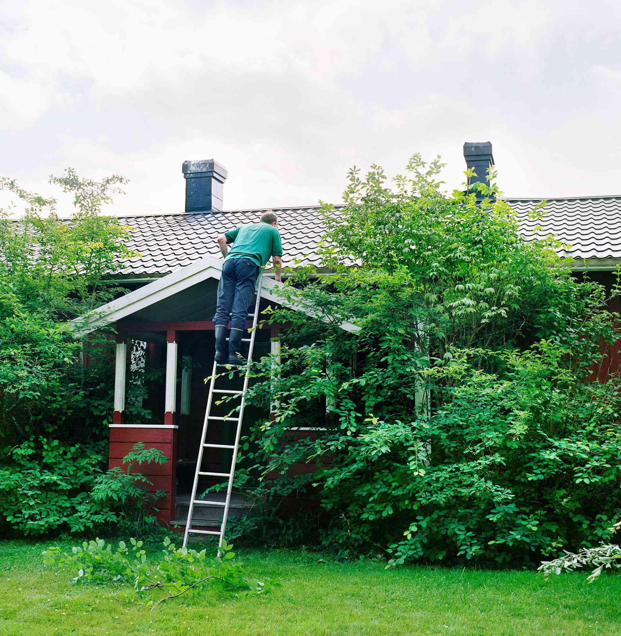Man climbing ladder to roof