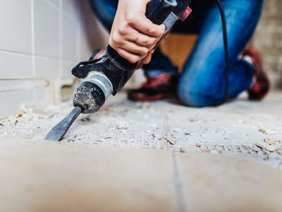 Woman removing old tiles