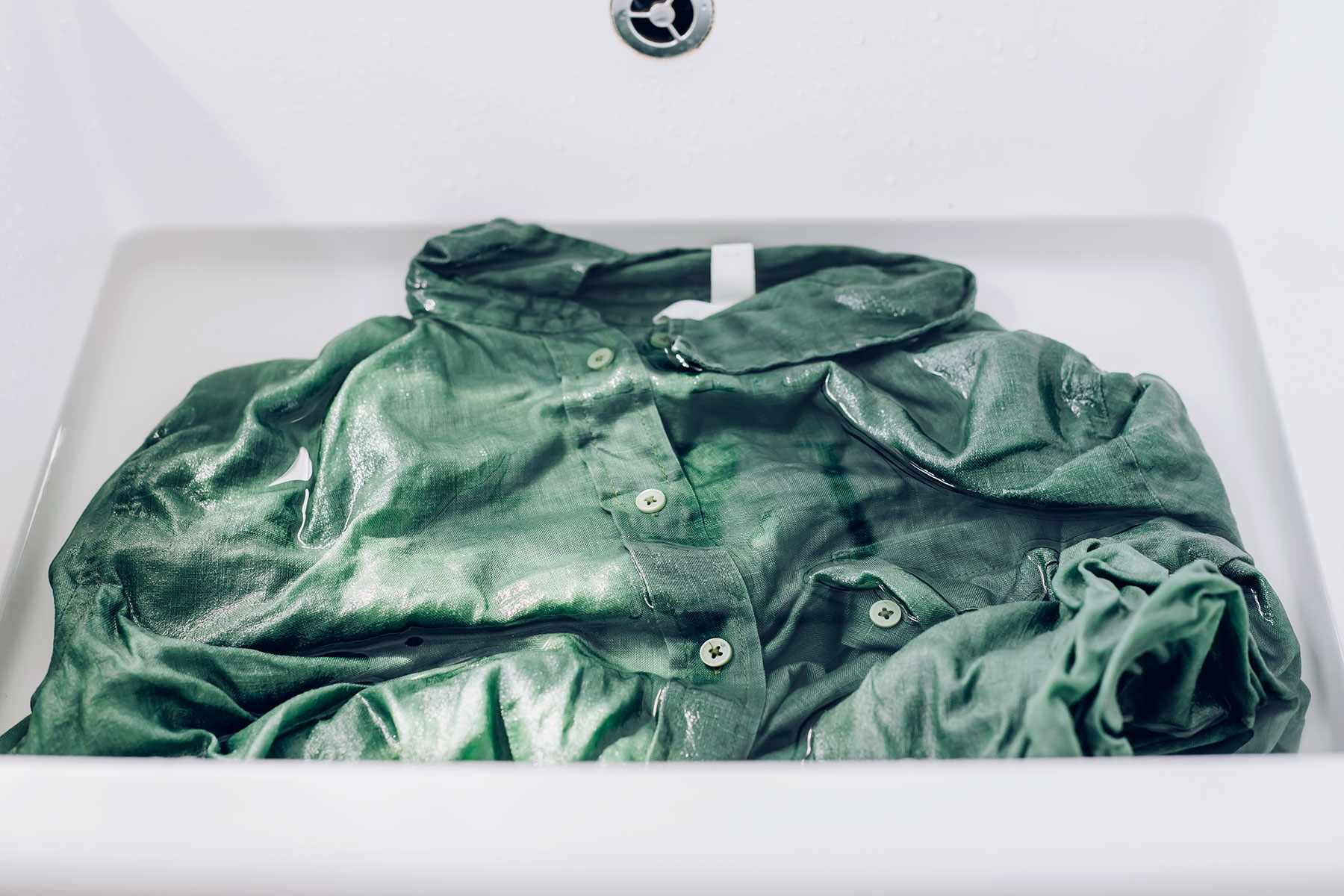 Green shirt placed in sink and soaking in water with oxygen-based bleach solution