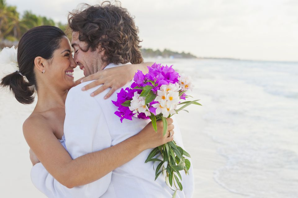 Happy bride and groom hug on beach