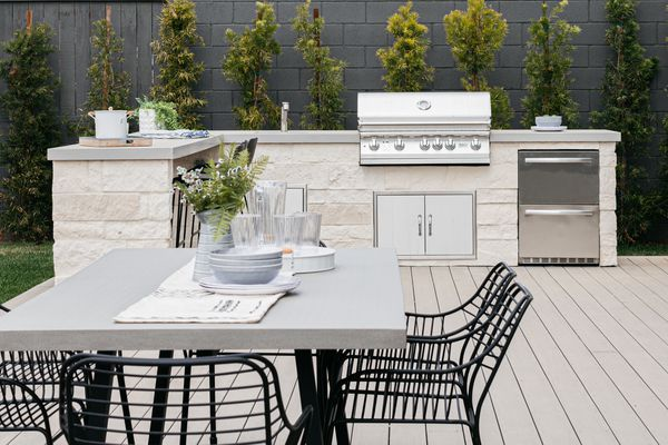 White stoned outdoor kitchen with sink and grill behind dining table