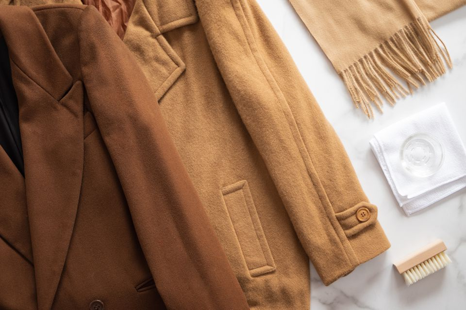 Brown and tan wool coats laid on white surface next to tan wool scarf, soft-bristled brush and glass on white cloth