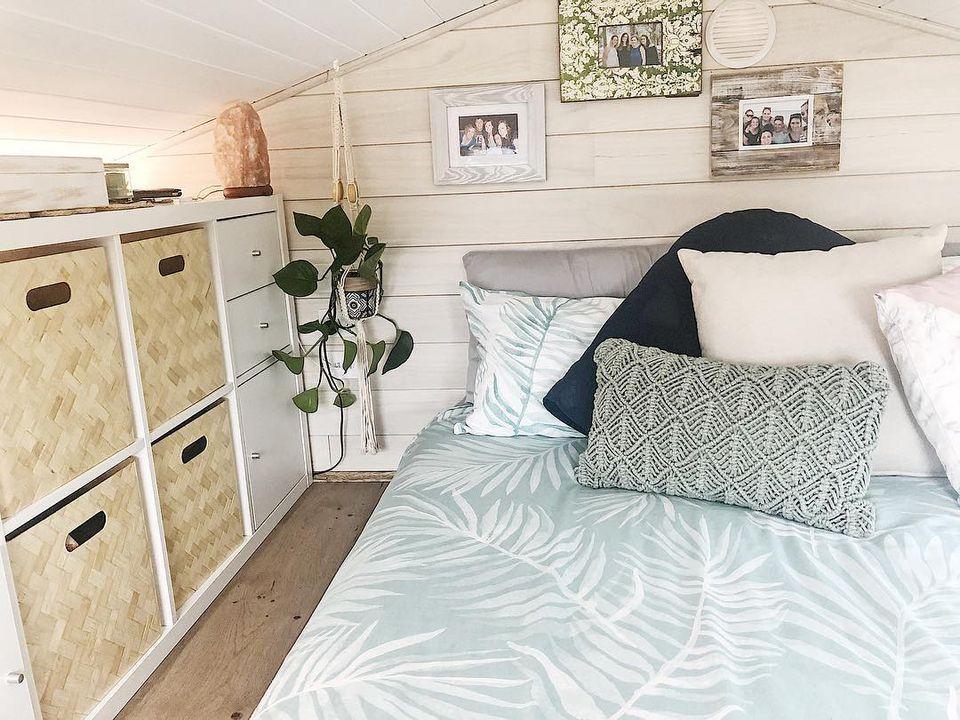 Una pequeña habitación en casa con paneles de madera blanca, edredón de palma de aguamarina y cestas