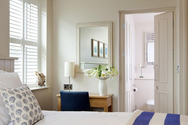 Bright bedroom with mirror and flowers
