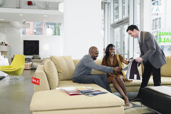Salesclerk showing fabric samples to man and woman in furniture store