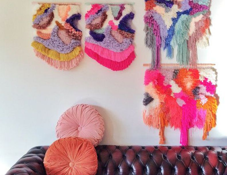 Macrame tapestries above leather couch.