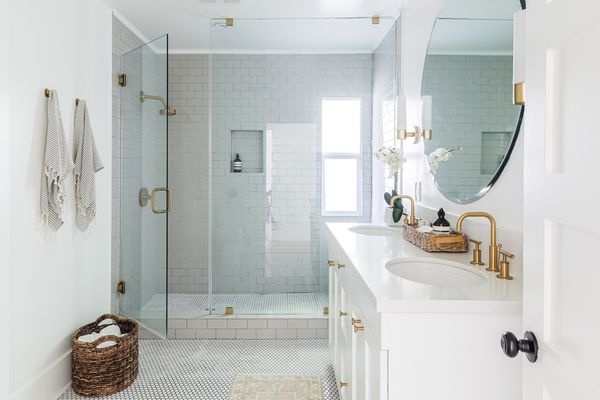 White bathroom with minimal decor items and open glass shower door