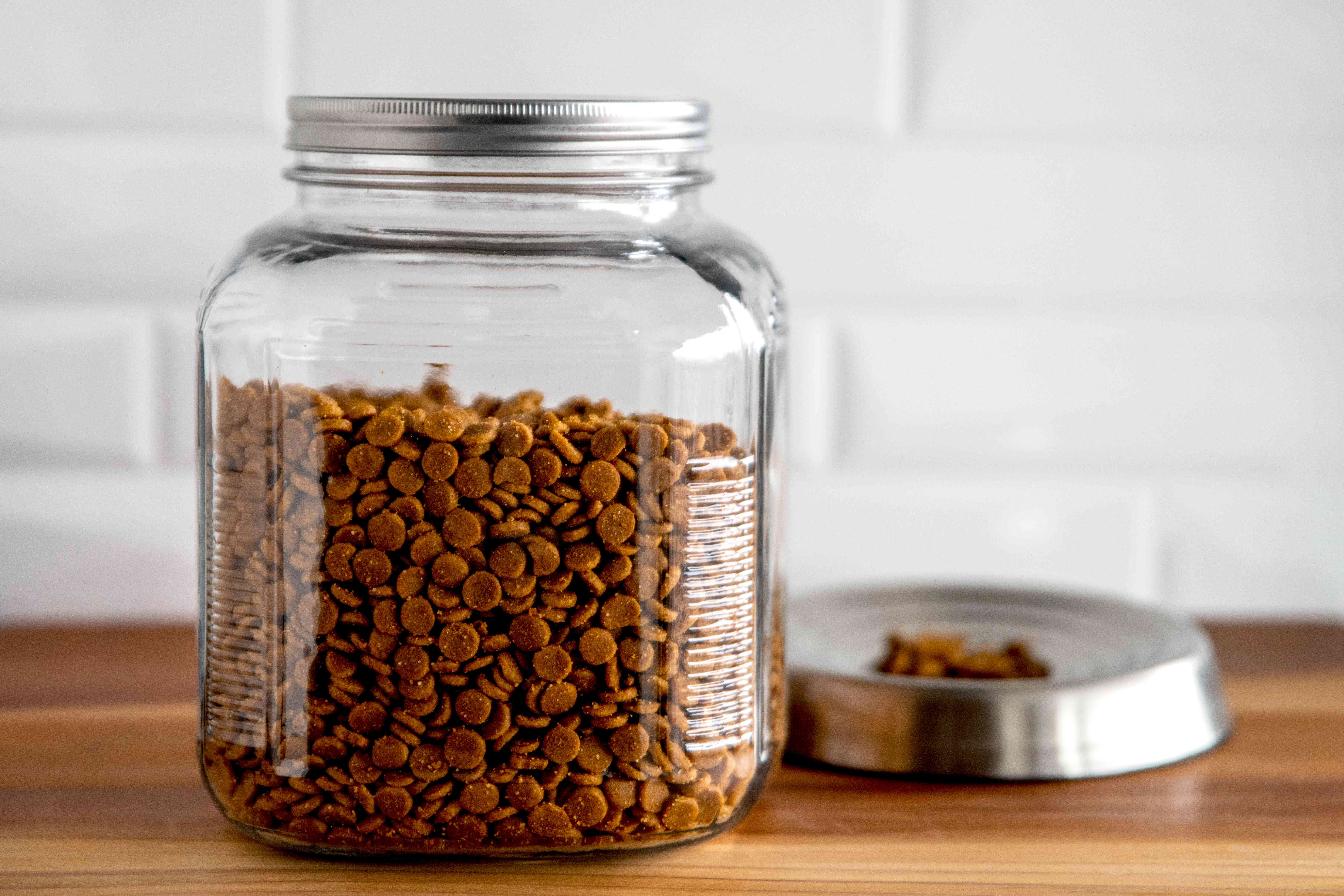 Pet food stored in closed glass container next to pan with some dog food pieces