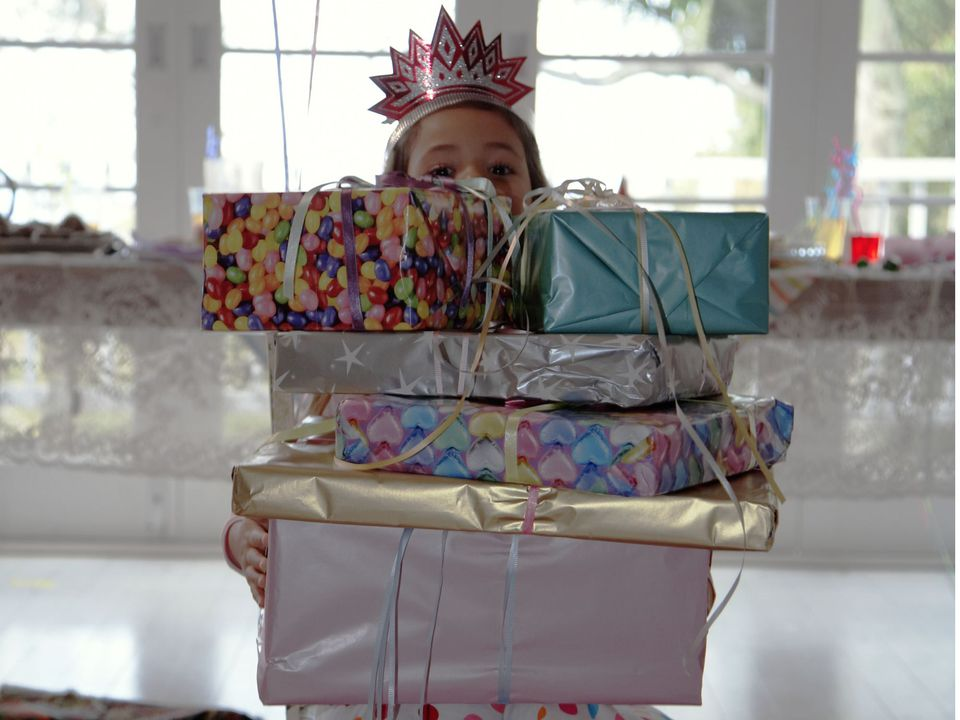 A picture of a child with birthday presents
