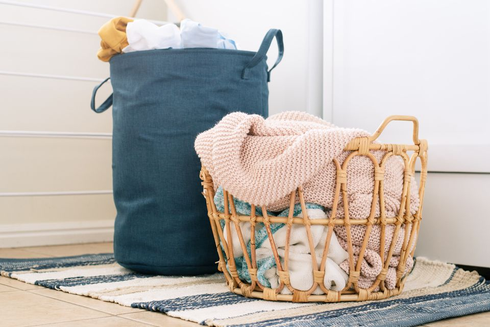Woven laundry basket and cloth hamper full of clothes on rug