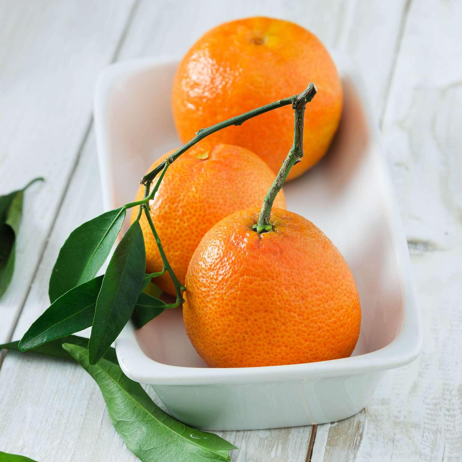 un tazón de naranjas frescas en una mesa blanca