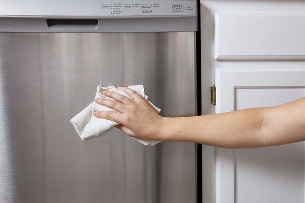 person wiping a stainless steel dishwasher