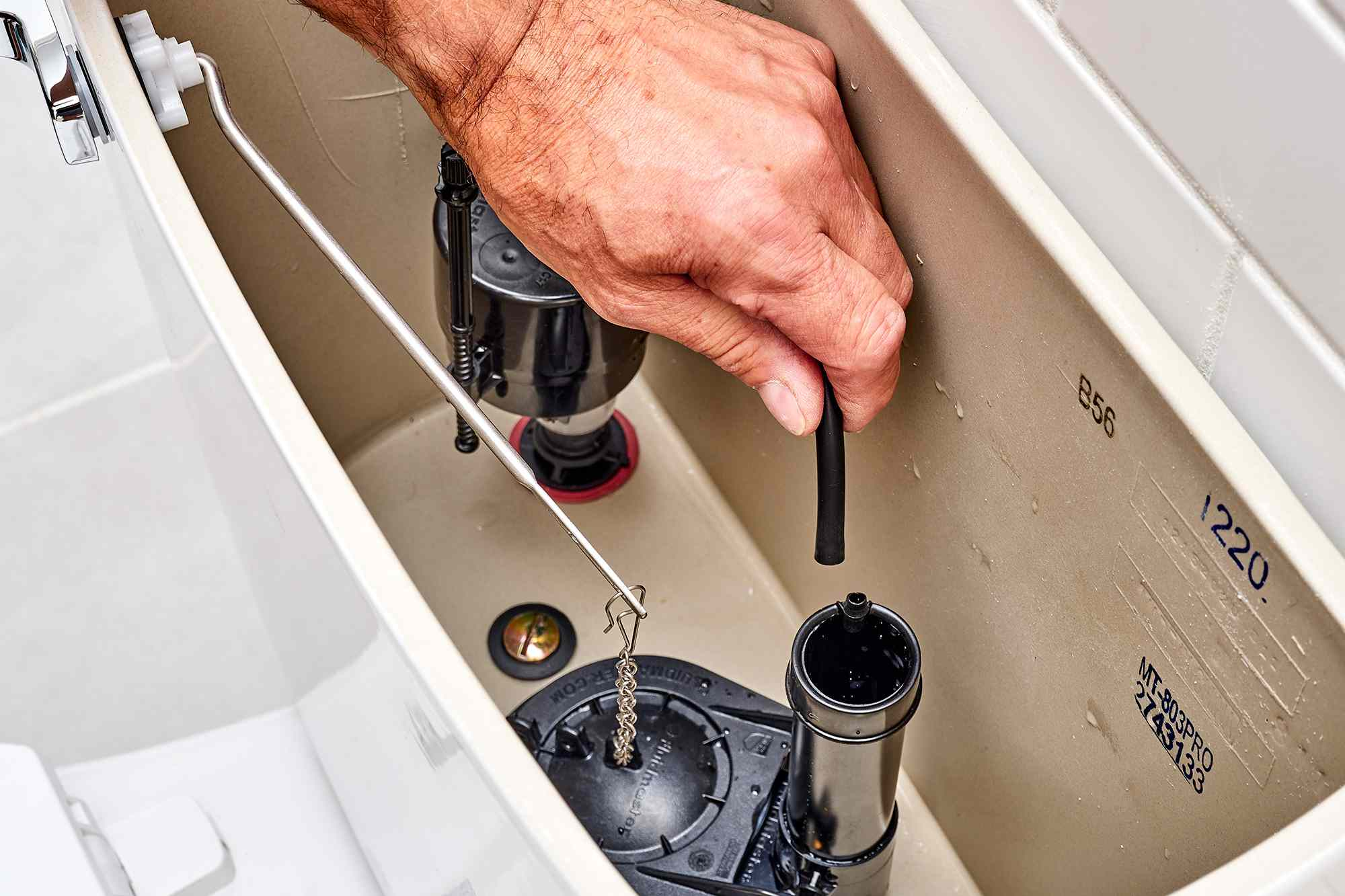 Rubber fill tubing connected onto top of fill valve in toilet tank