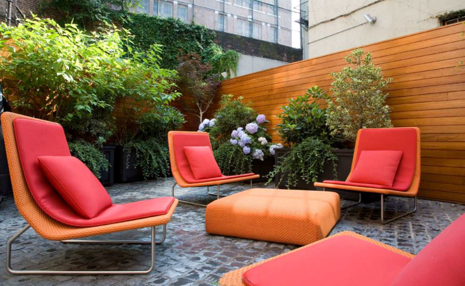 Vertical garden near wooden wall highlighted by orange and red furniture.