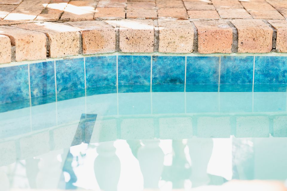 Water line on inside of blue pool lining with a brick floor on top closeup