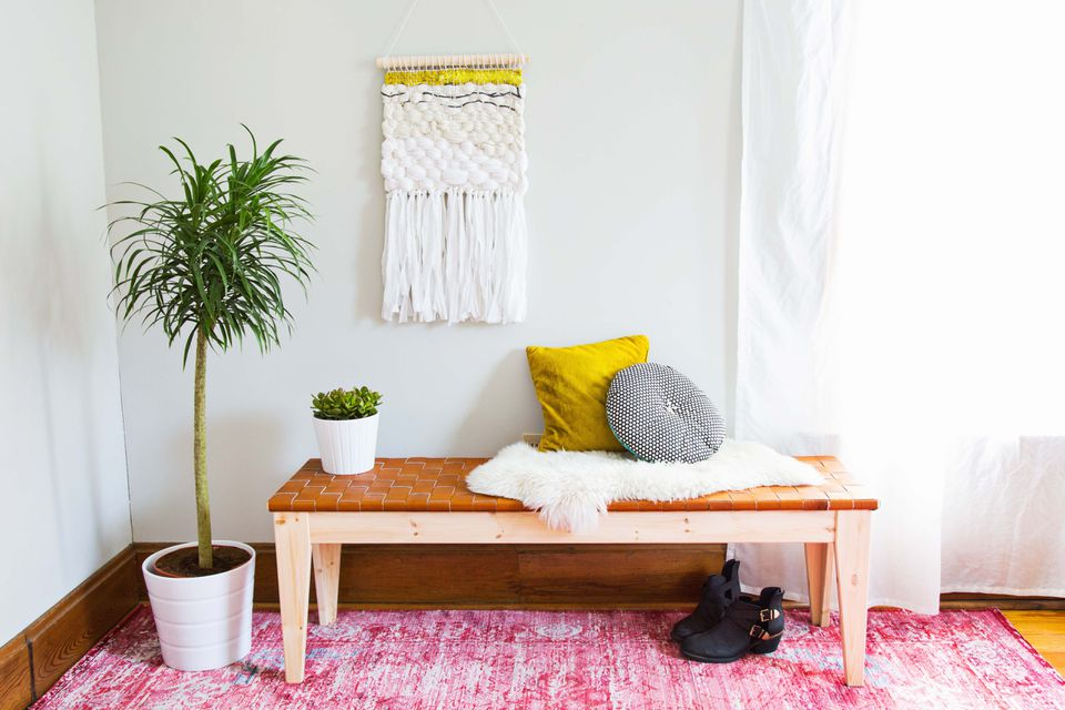 A living room with a bench, pillows, and a wall hanging