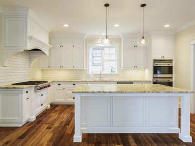 White Retro Style Kitchen with Wood Floor and Island