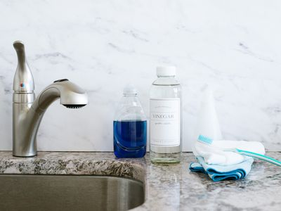 Bathroom faucet next to dish soap and vinegar bottles and folded towels with toothbrush on top